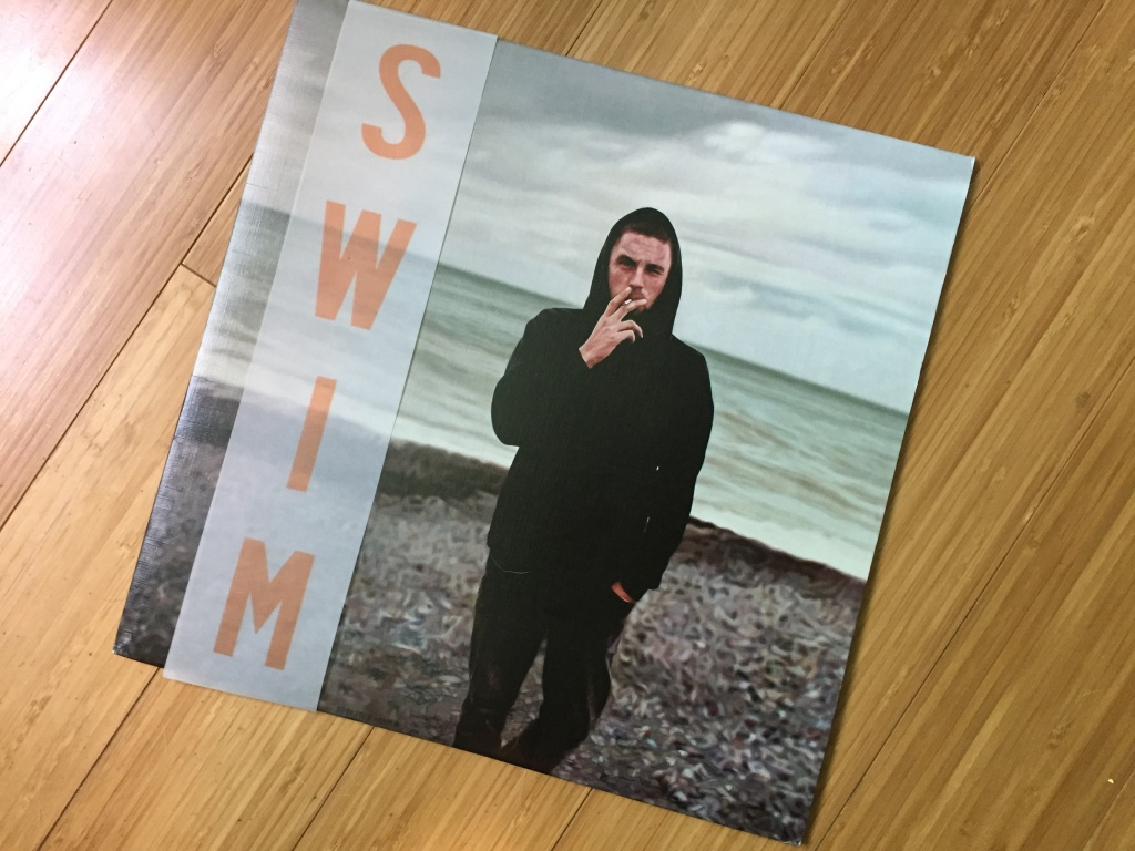 Swim by Die! Die! Die! album on a wood floor